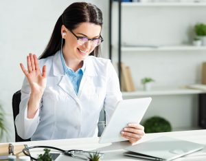 positive doctor waving and having online consultation on digital tablet in clinic office with laptop